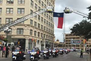 A Texas flag is hung from fire trucks by Alamo Plaza for the funeral procession for San Antonio firefighter Greg Garza, Thursday, Oct. 24, 2019.