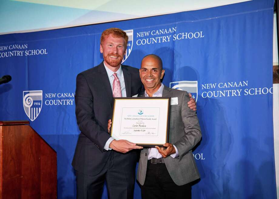 New Canaan Country School's Head of School Aaron Cooper presents the O'Herron Faculty Award to Carlos Mendoza of Norwalk. Photo: Contributed photo Photo: Contributed Photo