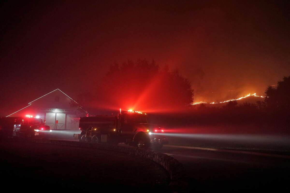 Firefighters stage near the Robert Young Winery as the Kincade Fire burns outside Geyserville, Calif., on Thursday, October 24, 2019.