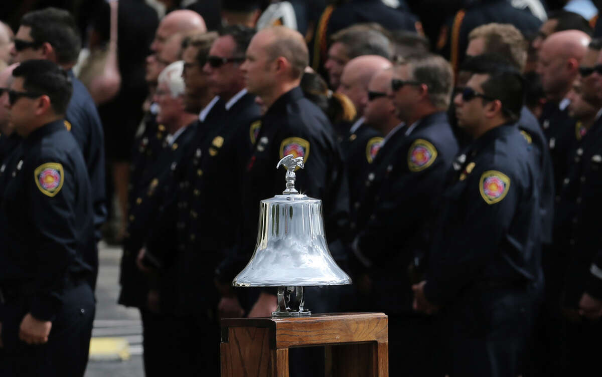 Firefighters stand near a bell to be rung for the funeral service for San Antonio firefighter Greg Garza at Community Bible Church on Thursday, Oct. 24, 2019. Firefighters from SAFD and surrounding areas including other first responders gathered at the church to honor Garza who died last week while on duty. A mass was held inside the church and then a traditional firefighters honors service with bagpipes, a 21-gun salute and flyover was held before Garza was taken to a private burial service. (Kin Man Hui/San Antonio Express-News)