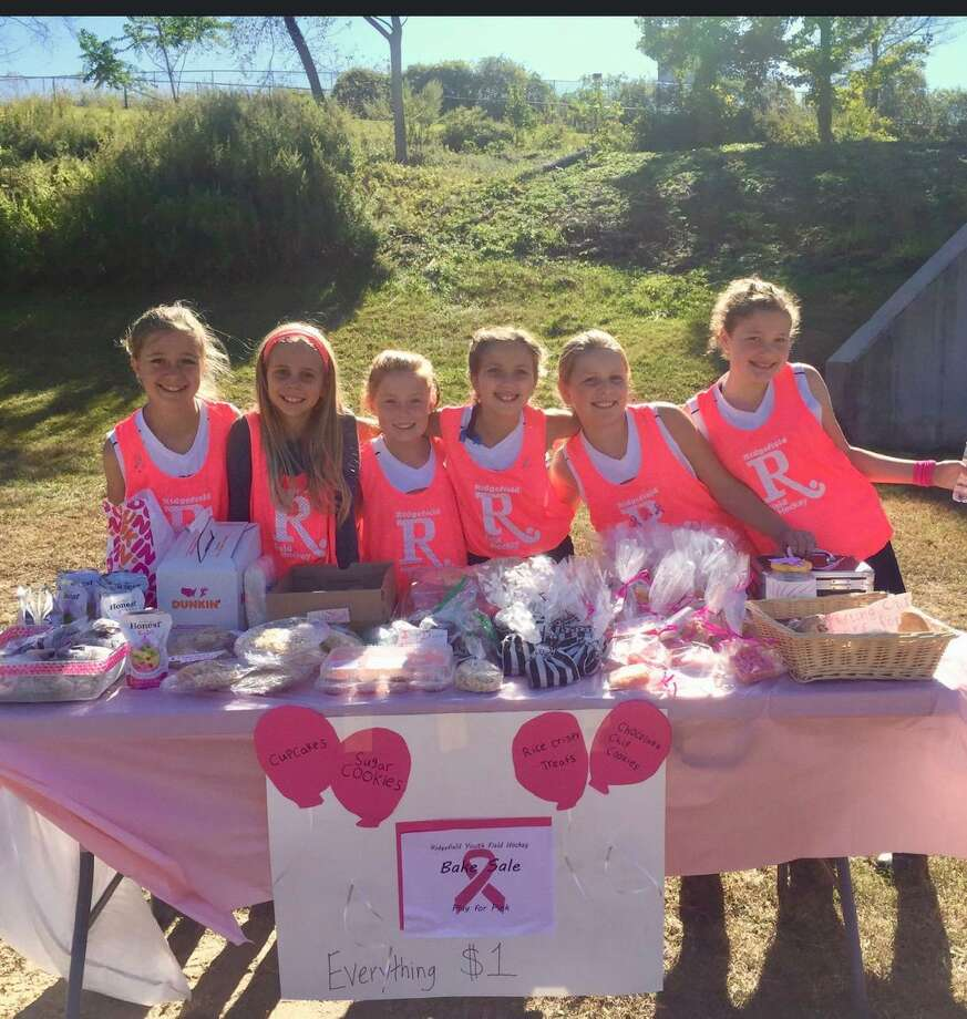 Ridgefield youth field hockey players at their bake sale table in front of Tiger Hollow on Oct. 19. Photo: Contributed Photo