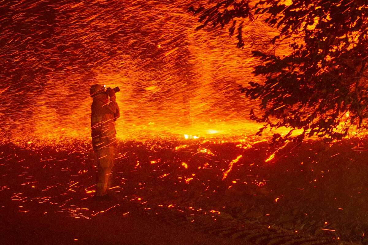 A photographer takes a photo amidst a shower of embers during the Kincade Fire near Geyserville, California on October 24, 2019. - The fire broke out in spite of rolling blackouts by utility companies in both northern and Southern California.