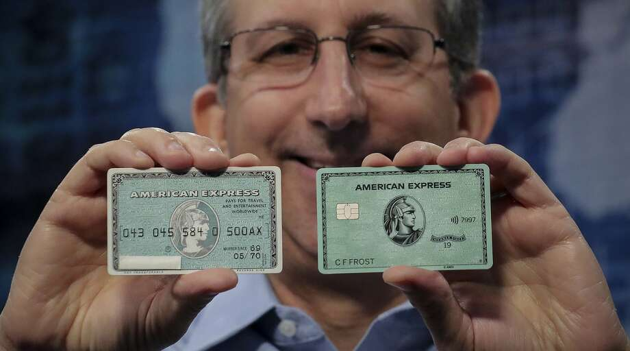 "In this Wednesday, Oct. 23, 2019, photo Ira Galtman, American Express director of corporate archives, shows the original American Express ""Green Card,"" left, with its latest version in New York. For 50 years the ""Green Card"" was everywhere and has been revamped, with a new look and more travel benefits. (AP Photo/Bebeto Matthews) Photo: Photos By Bebeto Matthews / Associated Press"