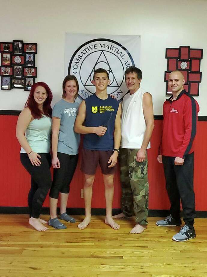 Pictured, from left, are Haley Northup, Laurie Bennett, new Combat Martial Arts black belt Lucas Kindy, Craig Sira and Jacob Sira. Northup, Bennett, and Jacob Sira are part of the CMA Evaluation Board. Jacob Sira is also a certified CMA instructor.