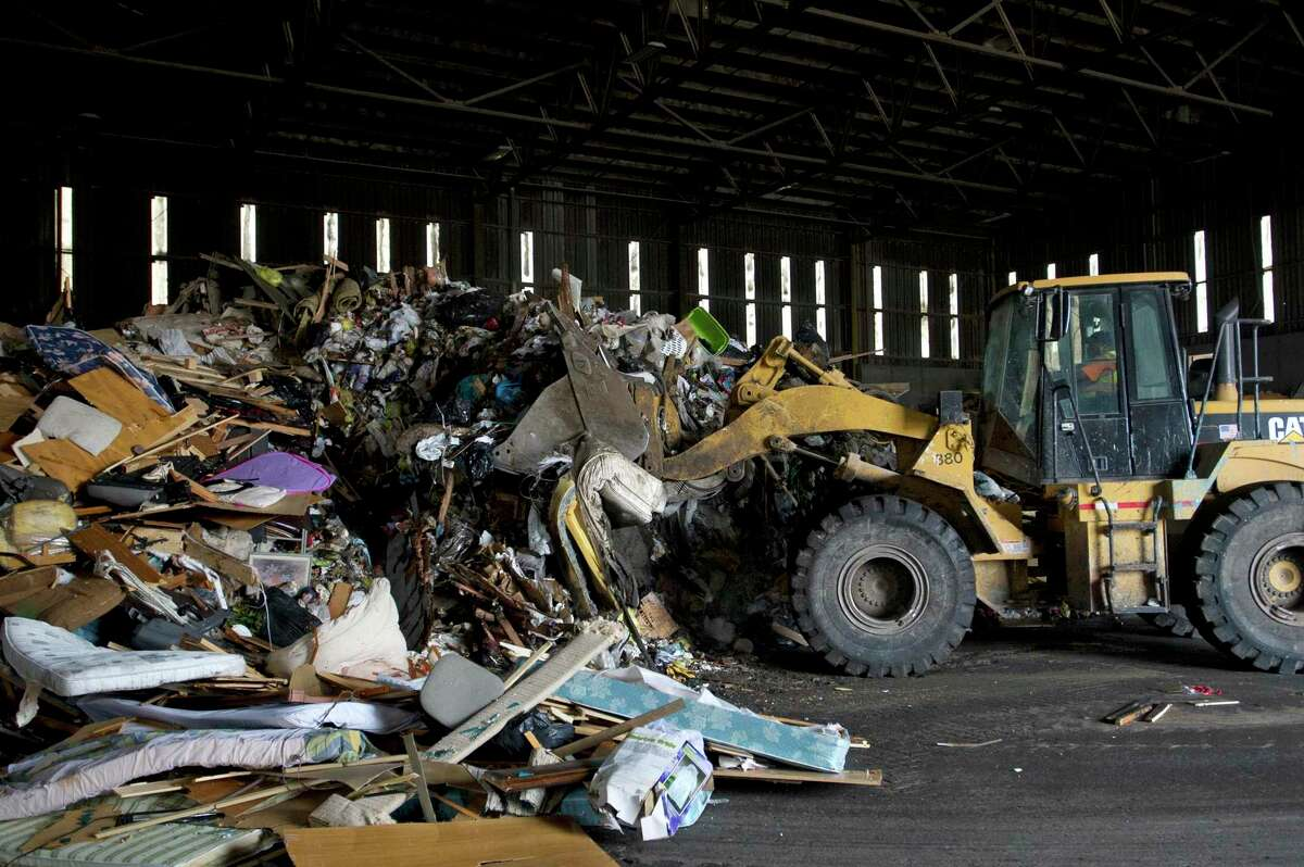 A large pile of garbage gets condensed by a front loader at the Stamford Transfer Station on Harborview Avenue in Stamford, Conn.