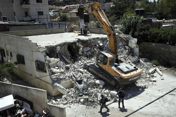 FILE - In this Aug. 21, 2019 file photo, Israeli authorities demolish a Palestinian owned house in east Jerusalem. A rights group says Israeli authorities have demolished at least 140 Palestinian homes in east Jerusalem this year, the highest annual number since it began keeping records in 2004. The demolition of homes built without permits comes amid a major increase in Jewish settlement activity both in east Jerusalem and in the occupied West Bank since U.S. President Donald Trump took office.