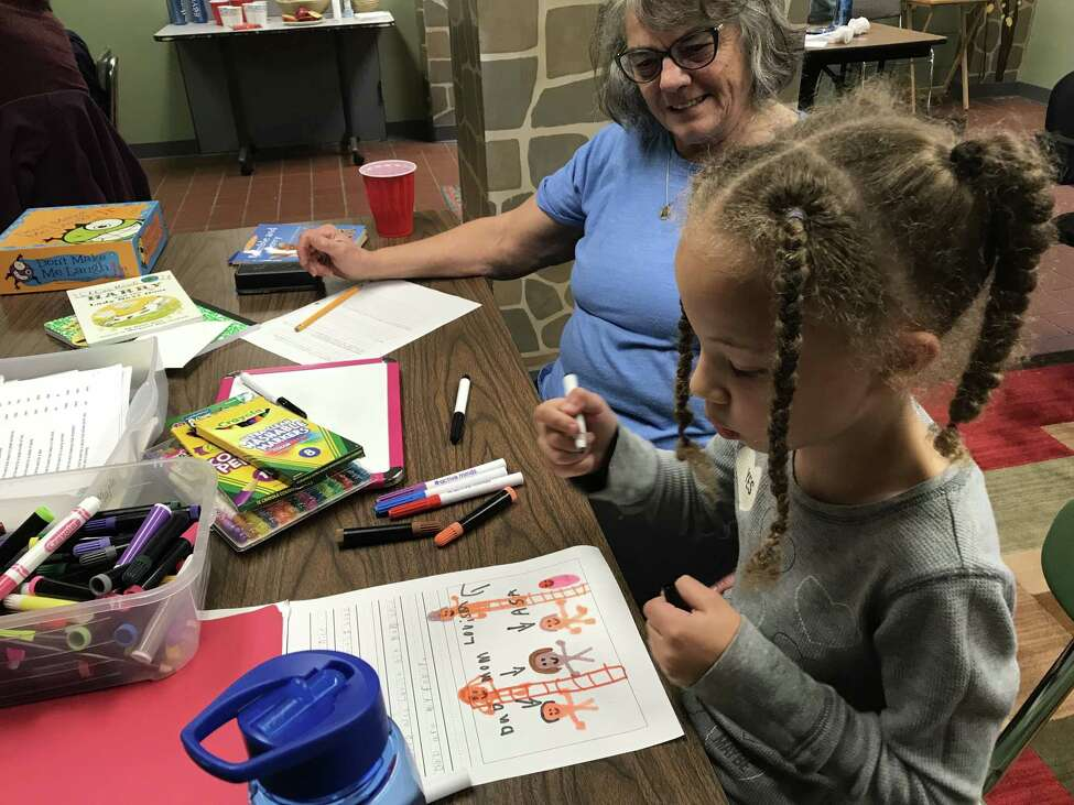 Tutor Nancy Ost, left, with Maple Bee, a second-grader with the Wizard's Wardrobe reading program in Albany's South End (photo by Amy Biancolli)