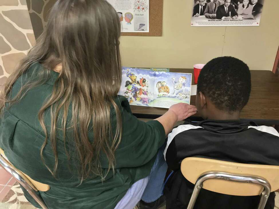 Tutor Laurie Bonesteel, left, with second-grader Zaire Gordon in the Wizard's Wardrobe reading program in Albany's South End (photo by Amy Biancolli)