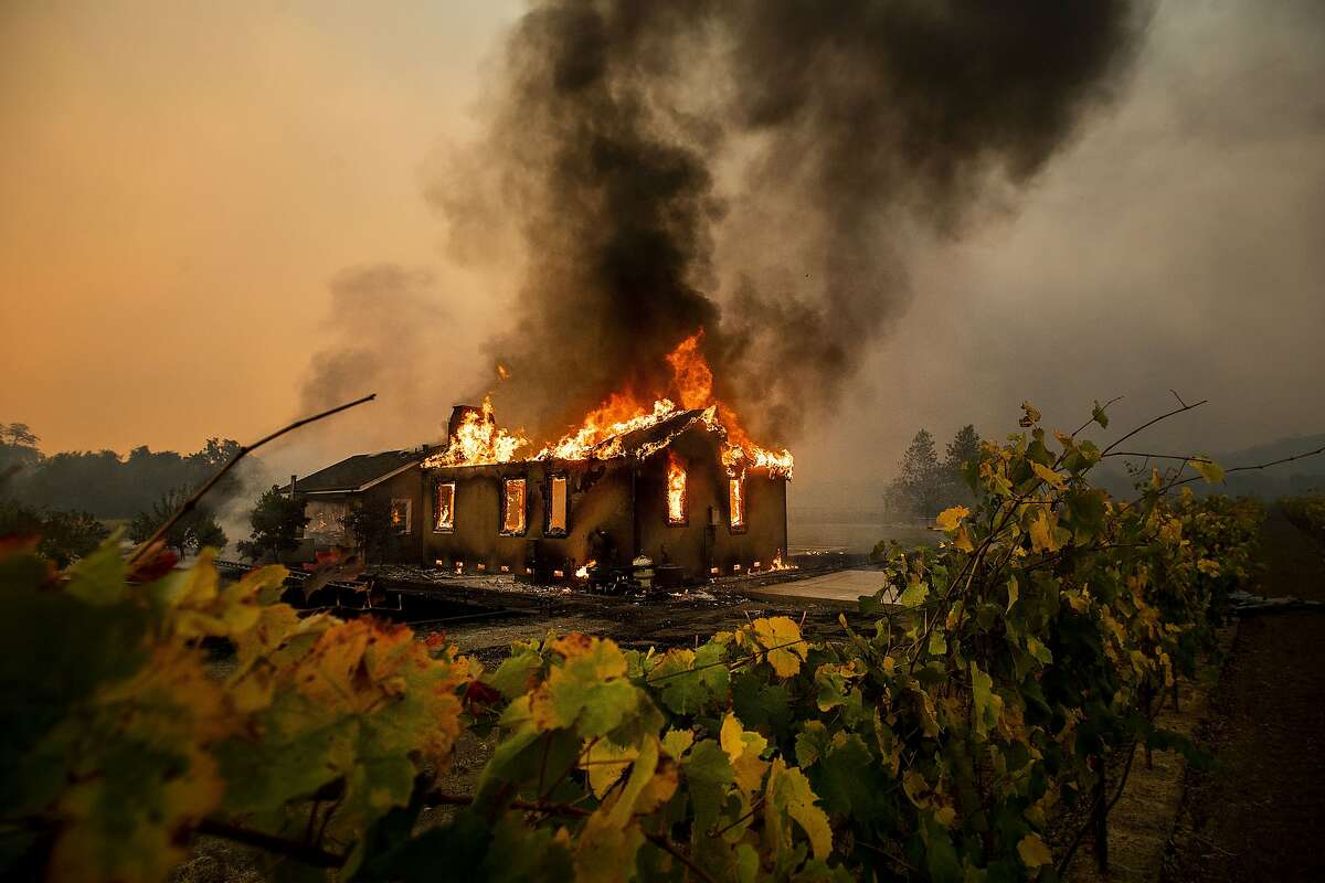 Vines surround a burning building as the Kincade Fire burns through the Jimtown community of unincorporated Sonoma County, Calif., on Thursday, Oct. 24, 2019. (AP Photo/Noah Berger)