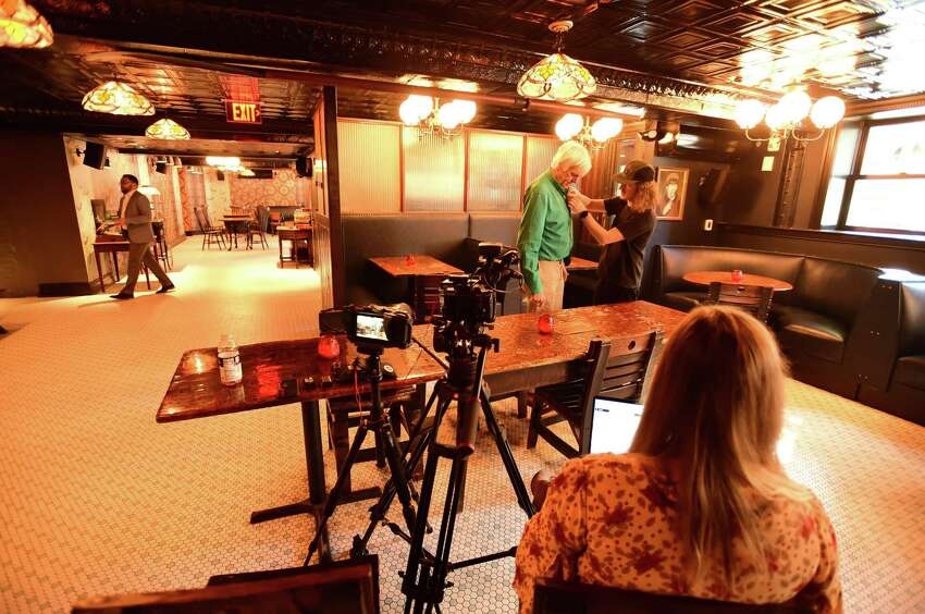 New Haven, Connecticut - Thursday, October 24, 2019: Video producers Ellie Brzezenski of the Graduate Hotel, right, with creative director Zach Goldstein of New York City putting a microphone on New Haven Register columnist / reporter Randall Beach for an interview Thursday on the history and memories of the newly opened Old Heidelberg bar on Chapel street in New Haven. The Old Heidelberg bar is in the same building as the boutique Graduate Hotel, formally the Duncan Hotel, which had its grand opening Thursday.