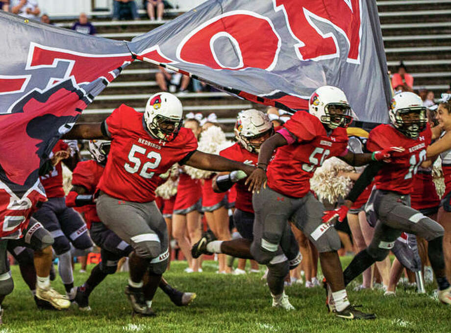 Alton's Kahron Edwards (52), Ihzel Brown and Alero Watson (10) bust through the banner to lead the Redbirds onto the field at Public School Stadium before a Sept. 13 game vs. Collinsville in Alton. The 3-5 Redbirds are back home Friday to end their season against DeKalb. Photo: Nathan Woodside / The Telegraph