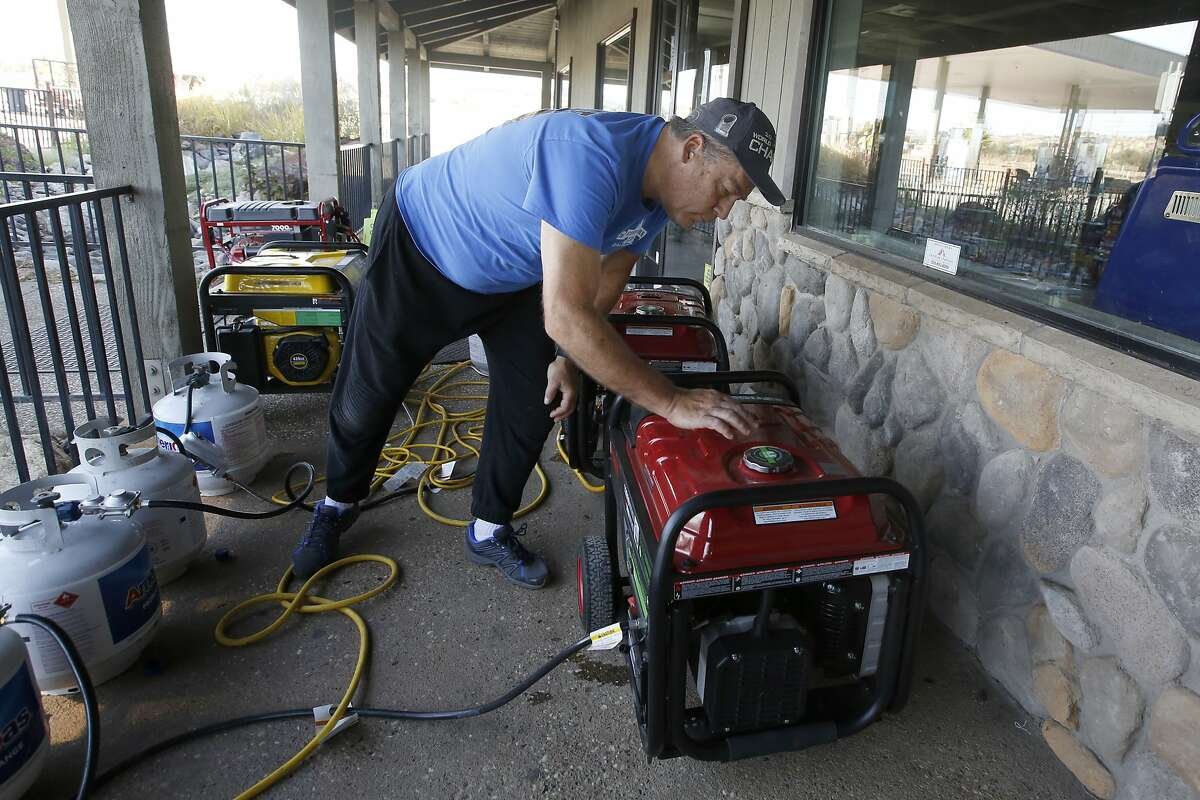 Brian Boyd checks one of the generators used to provide power at the Clear Creek Crossing store near Paradise, Calif., Thursday, Oct. 24, 2019. The Pacific Gas & Electric Co. cut power to 17 counties in Northern California to help prevent wildfires caused by downed power lines. Boyd said generators were brought to the store to provide power to the refrigerators and to provide some service to area residents. (AP Photo/Rich Pedroncelli)