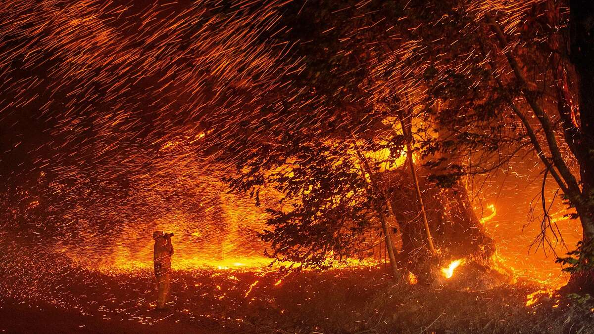 A photographer takes photos amidst a shower of embers as wind and flames rip through the area during the Kincade fire near Geyserville, California on October 24, 2019.