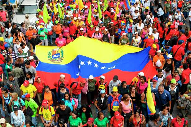 Supporters of Venezuelan President Nicolas Maduro participate with a fig Venezuelan national flag in a march in solidarity with the social movements that have exploded in Latin American countries in the last days, in Caracas, on October 24, 2019. - Thousands of government supporters paraded down a main avenue to show their support for the protests in Chile, Honduras, Ecuador, and to support Bolivian President Evo Morales. (Photo by Yuri CORTEZ / AFP) (Photo by YURI CORTEZ/AFP via Getty Images)