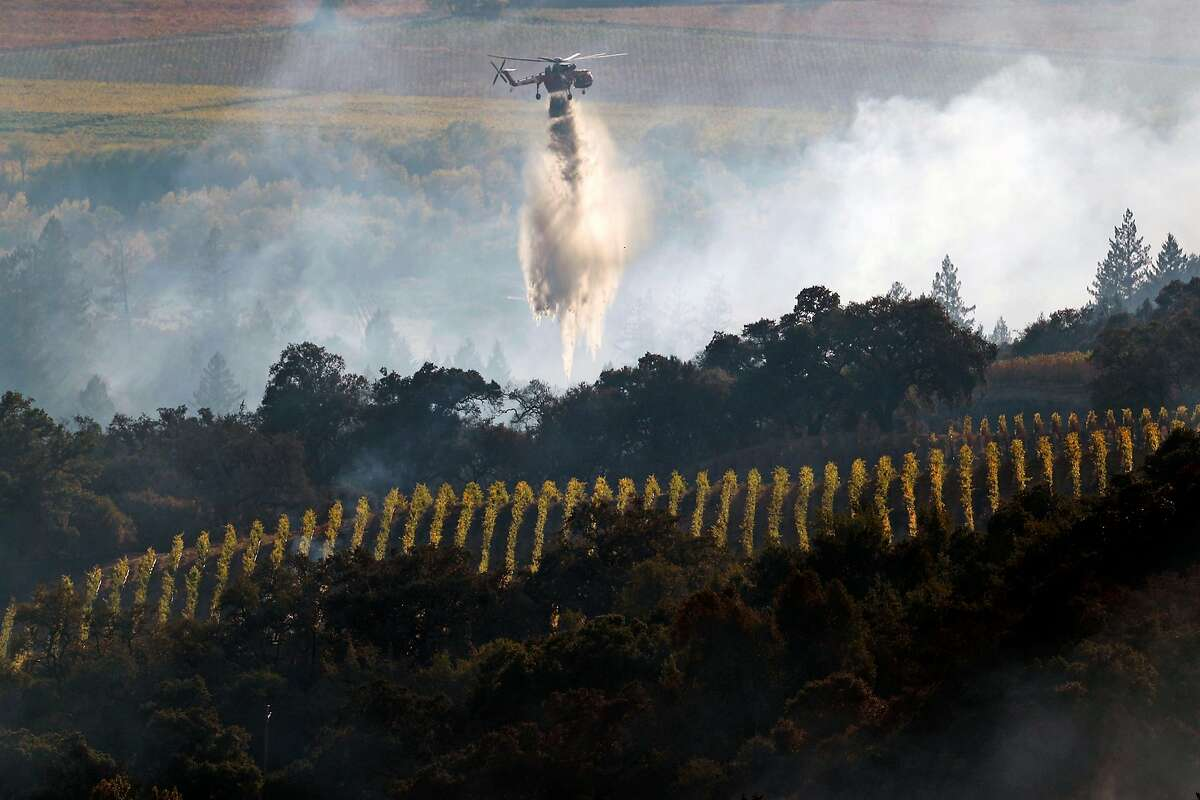 A helicopter drops water near a vineyard during Kincaid Fire in Geyserville, Calif., on Thursday, October 24, 2019.