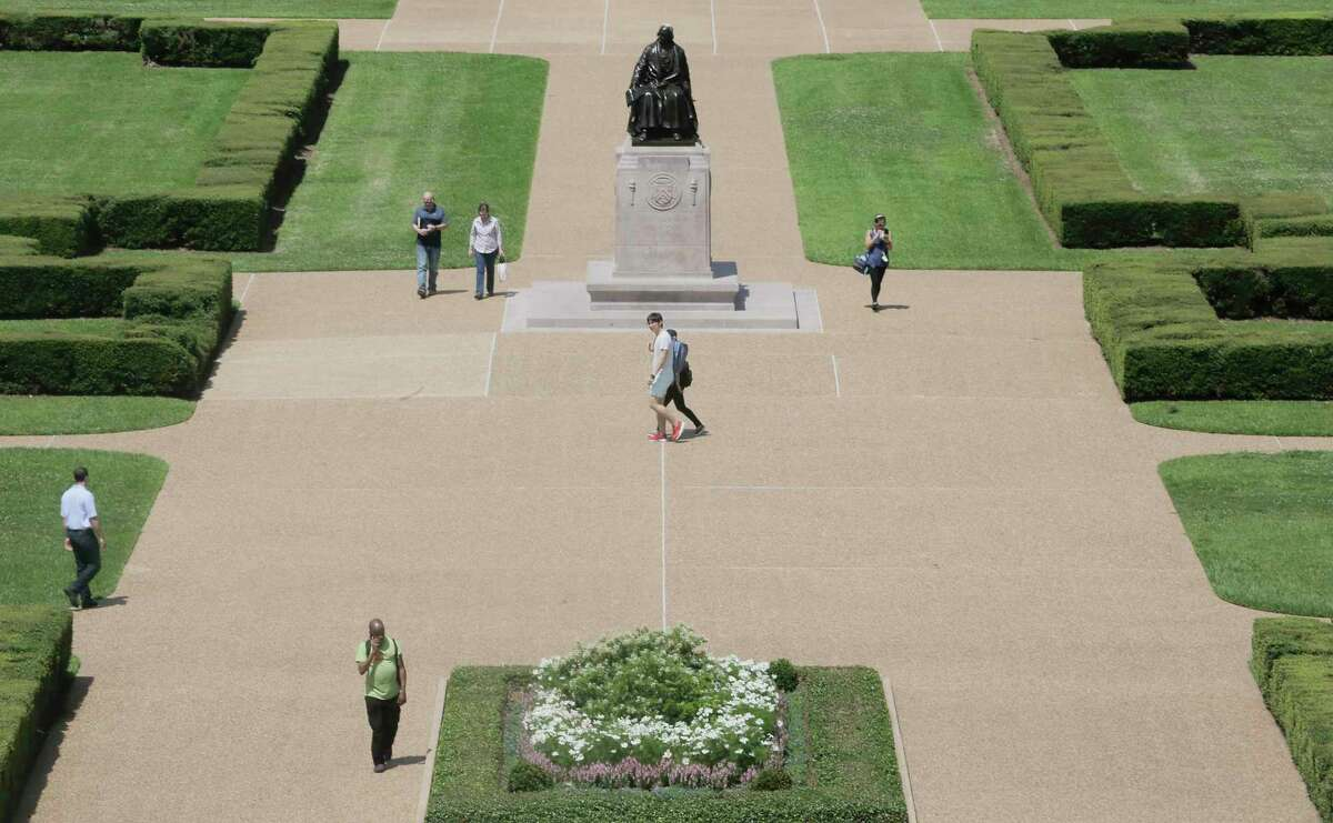 People walk by the statue of Rice University founder William Marsh Rice on campus on Friday, June 7, 2019 in Houston. Rice University started a new task force, which will explore its history and connections to slavery, segregation and racial injustice.
