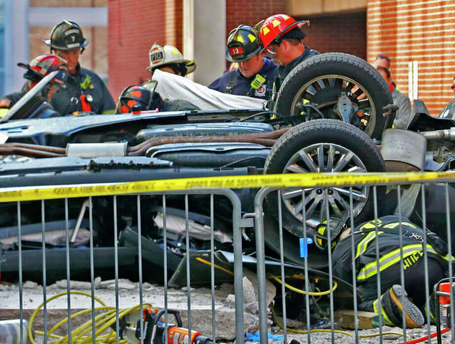 Indianapolis Fire Department personnel examine a vehicle that plummeted from an upper level of a parking garage in Indianapolis, killing two people inside. Photo: Kelly Wilkinson | Indianapolis Star (AP)
