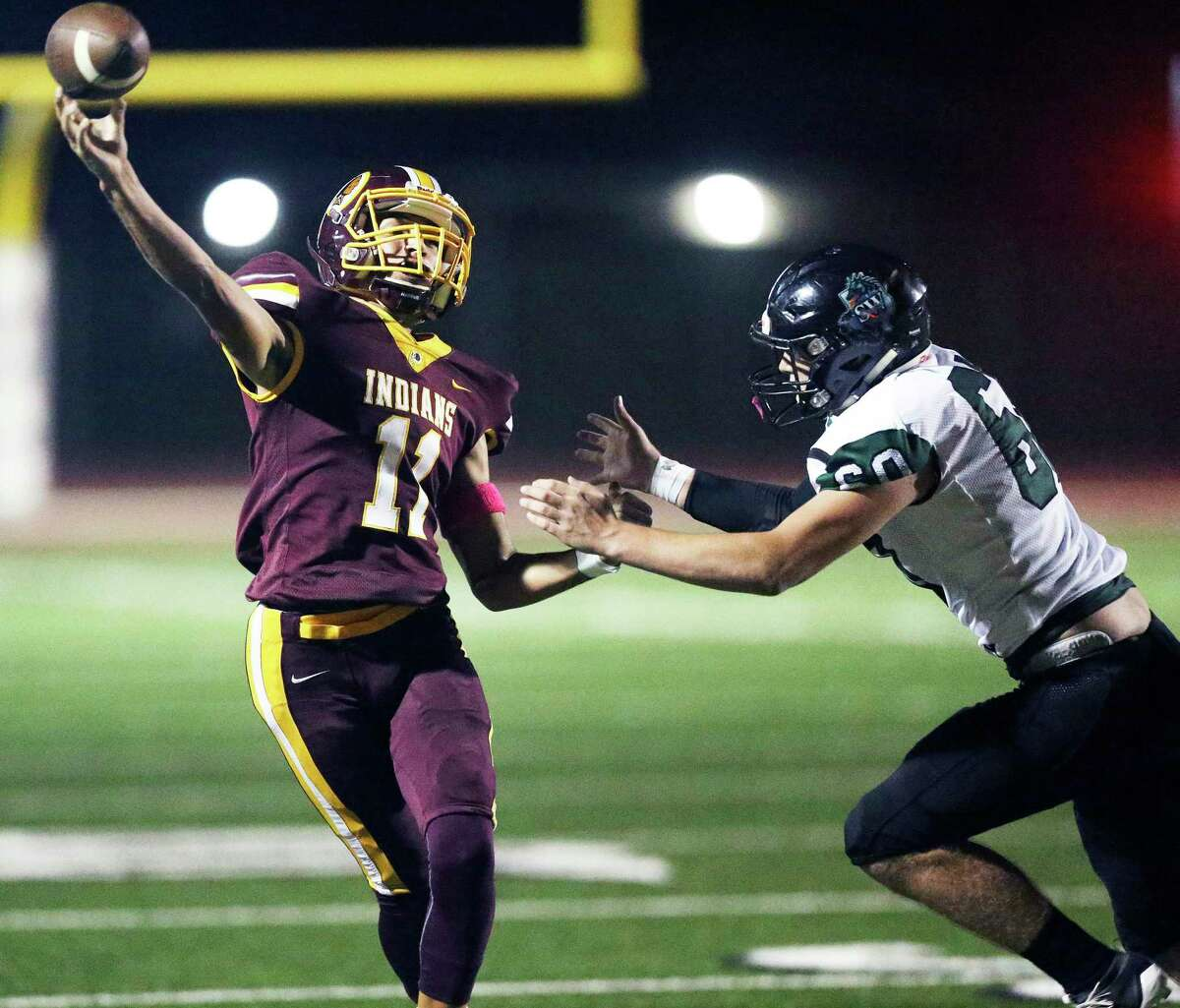Indians quarterback Joseph Rodriguez gets off a pass under pressure from Zach West as Harlandale hosts Southwest at Harlandale Stadium on 24, 2019.