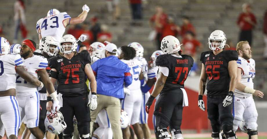 Houston Cougars offensive lineman Jack Freeman (75), offensive lineman Keenan Murphy (77) and offensive lineman Gio Pancotti (65) watch as the SMU Mustangs celebrate after beating the Houston Cougars in an NCAA football game at TDECU Stadium on Thursday, Oct. 24, 2019, in Houston. Photo: Jon Shapley/Staff Photographer