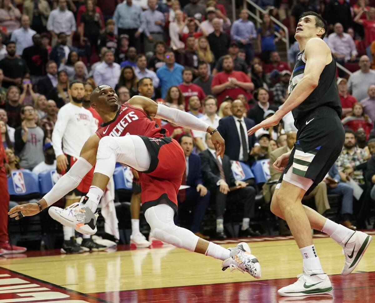 Houston Rockets Russell Westbrook falls to the floor after being fouled by Milwaukee Bucks Ersan Ilyasova during second half of NBA game at Toyota Center Thursday, Oct. 24, 2019, in Houston.
