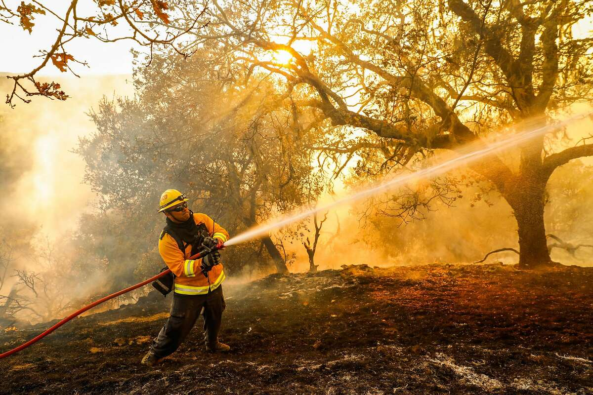 Firefighter Carlos Gonzalez with the Marin County Strike team hoses off flames to protect homes during the Kincade Fire in Geyserville, Oct. 24, 2019.