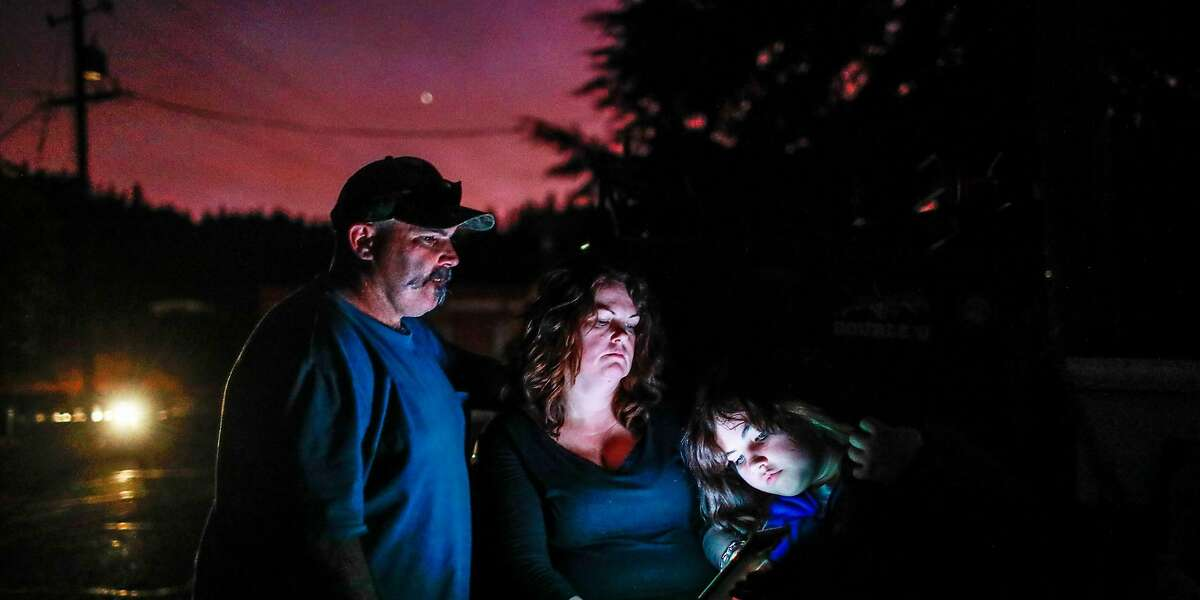 """(l-r) Aaron Johnson, wife Tammy White and daughter Leah Johnson, 11, sit outside their house without electricity as they watch the news on their phone for updates about the nearby Kincade Fire in Geyserville, California, on Thursday, Oct. 24, 2019. Leah said, """"I'm just scared our house is going to burn if it jumps over the river""""."""