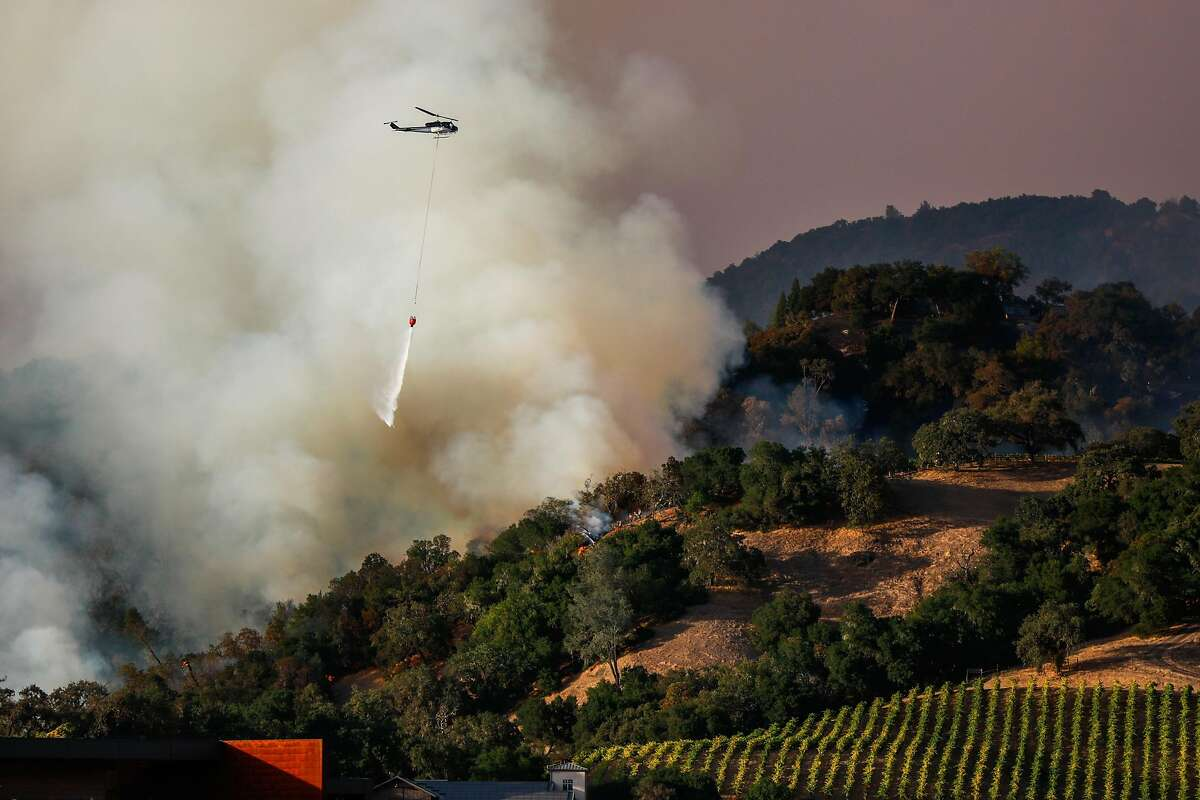 A plane drops water where firefighters worked to contain the Kincade Fire in Geyserville.