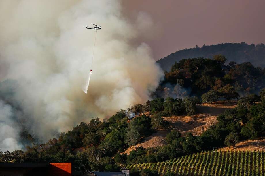 A plane drops water where firefighters worked to contain the Kincade Fire in Geyserville. Photo: Gabrielle Lurie / The Chronicle