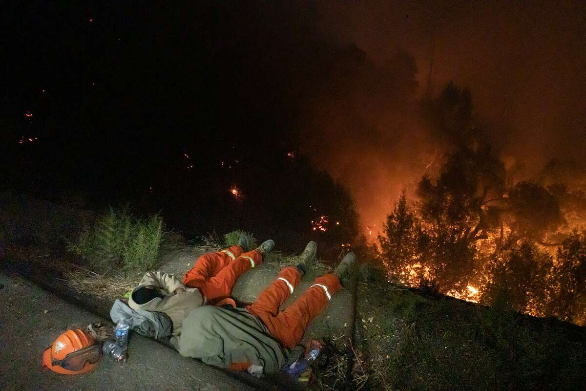 Pine Grove Youth Conservation Camp members sleep after two days of fighting fires near the River Rock Casino on Thursday, Oct. 24, 2019, in Geyserville, Calif.