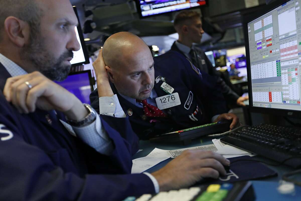 FILE - In this Oct. 2, 2019, file photo specialists James Denaro, left, and Mario Picone work on the floor of the New York Stock Exchange. The U.S. stock market opens at 9:30 a.m. EDT on Friday, Oct. 25. (AP Photo/Richard Drew, File)
