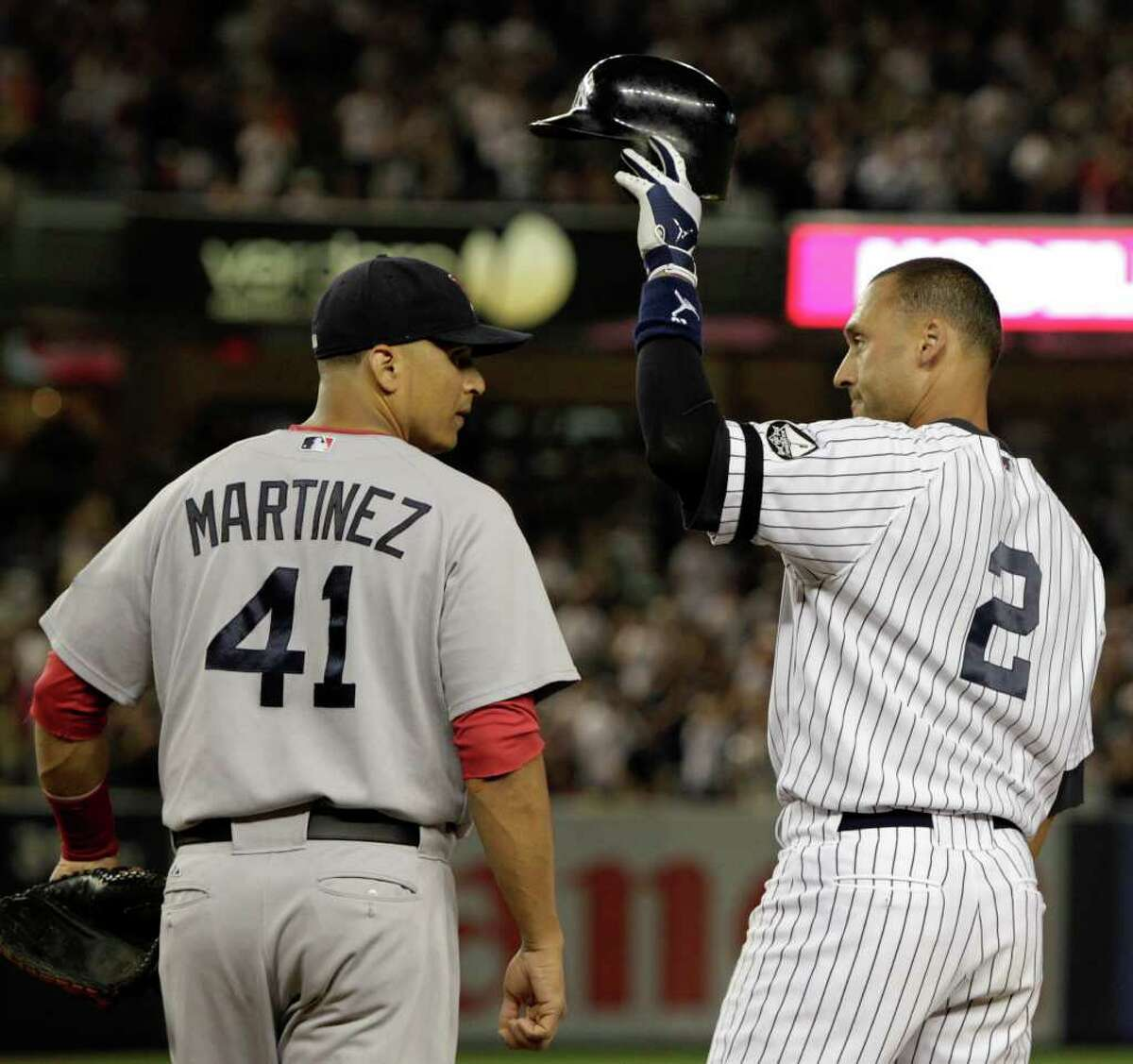 Boston Red Sox first baseman Victor Martinez (41) watches as New York Yankees Derek Jeter tips his cap to the crowd after hitting his 2,874th hit, a second-inning, RBI single, surpassing Babe Ruth on Major League Baseball's all time hits list, in their baseball game at Yankee Stadium on Sunday, Aug. 8, 2010 in New York. (AP Photo/Kathy Willens)