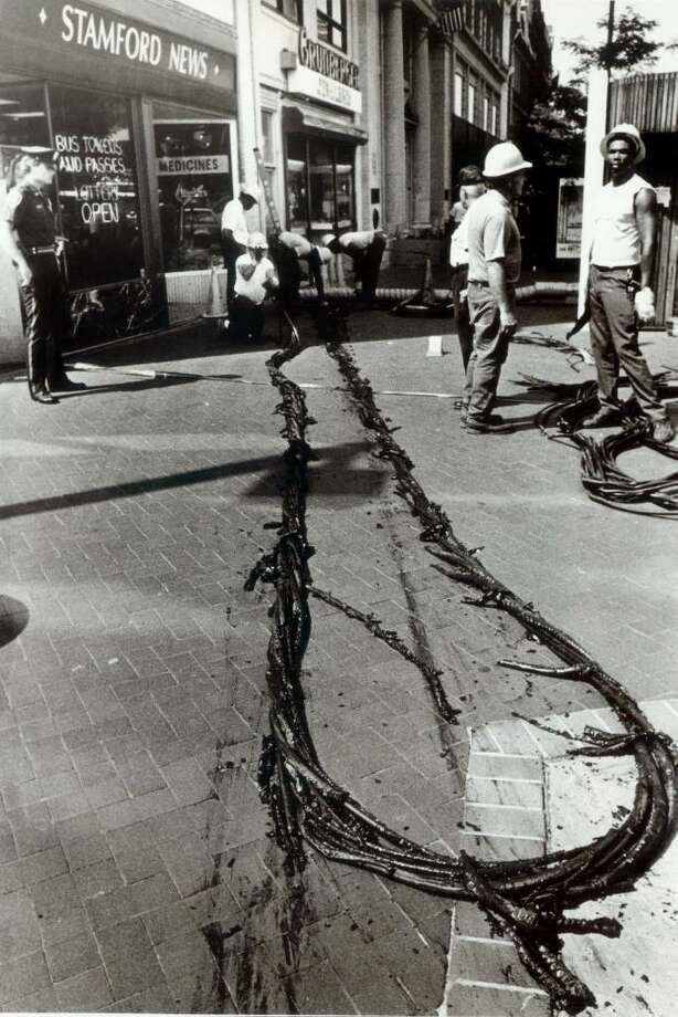 Aug. 13, 1985: An electrical fire in the basement of a downtown bank caused the evacuation of a partial block due to smoke and fumes. This burned cable was winched out of the manhole in the background. Photo: ST