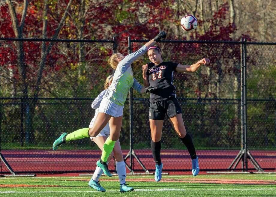 Wilton goalie Erynn Floyd punches the ball away from Ridgefield's Tasha Riek. Photo: Gretchen McMahon / For Hearst Connecticut Media / (C)2014