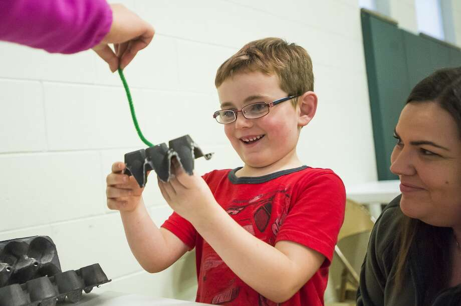 "Xavier Litchfield, 5, smiles after creating a ""bat"" out of an egg carton as his mother Melissa Brown, right, watches during a Halloween Bash hosted by Midland Recyclers Thursday, Oct. 24, 2019 at St. Brigid Catholic School. (Katy Kildee/kkildee@mdn.net) Photo: (Katy Kildee/kkildee@mdn.net)"