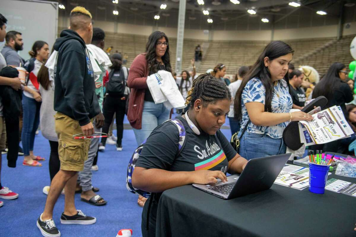"""High school senior Jala Willis, 18, signs up to """"save their seats"""" for free community college tuition after a Alamo Promise pep rally held Oct. 21."""