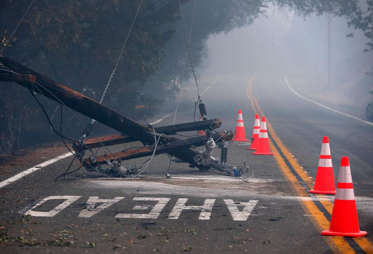 Safety cones surround a toppled utility pole on Geysers Road as the Kincade Fire continues to burn near Geyserville, Calif. on Friday, Oct. 25, 2019.