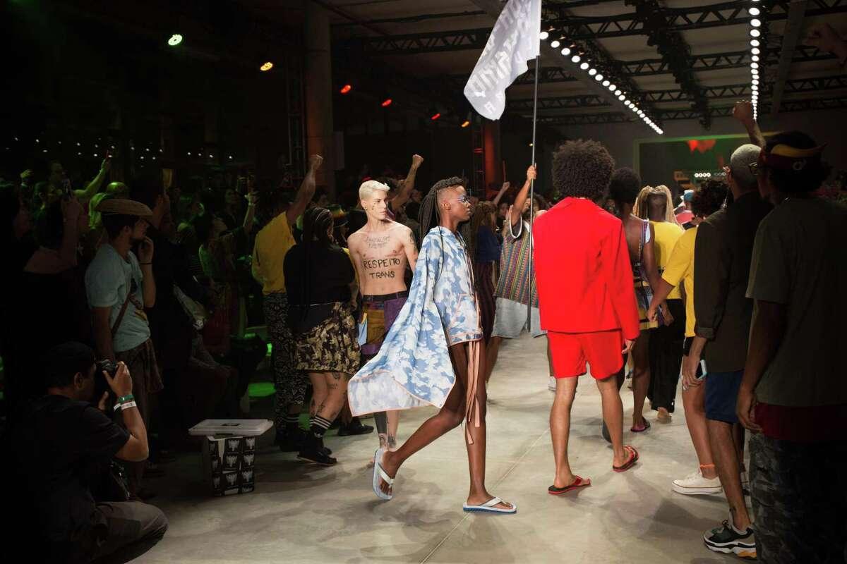 "Model Sam Porto on the catwalk for the Cavalera brand during Sao Paulo Fashion Week. The graffiti on his abdomen reads ""Trans respect."""