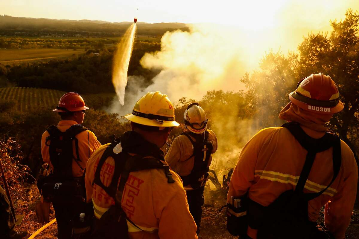Monterey Strike team firefighters watch over the Kincade Fire in Geyserville, California, on Thursday, Oct. 24, 2019.