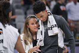 San Antonio Spurs assistant coach Becky Hammon talks to Spurs guard Dejounte Murray, right, after an NBA basketball game against the New York Knicks, Wednesday, Oct. 23, 2019, in San Antonio. San Antonio won 120-111. (AP Photo/Darren Abate)