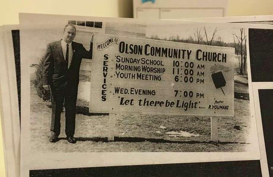 A community member stands next to a sign displaying service times at Olson Community Church when the late Rev. Robert Youmans was pastor. (Photo by Niky House)