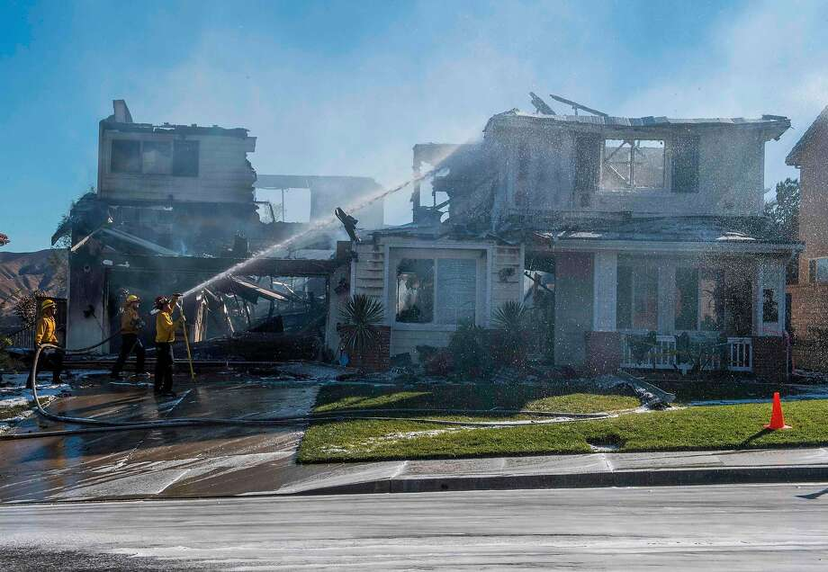 Firefighters hose down a burning house near Santa Clarita (Los Angeles County). Southern California Edison said it had cut off power to the area five hours before the fire broke out Thursday afternoon. Photo: Mark Ralston / AFP Via Getty Images