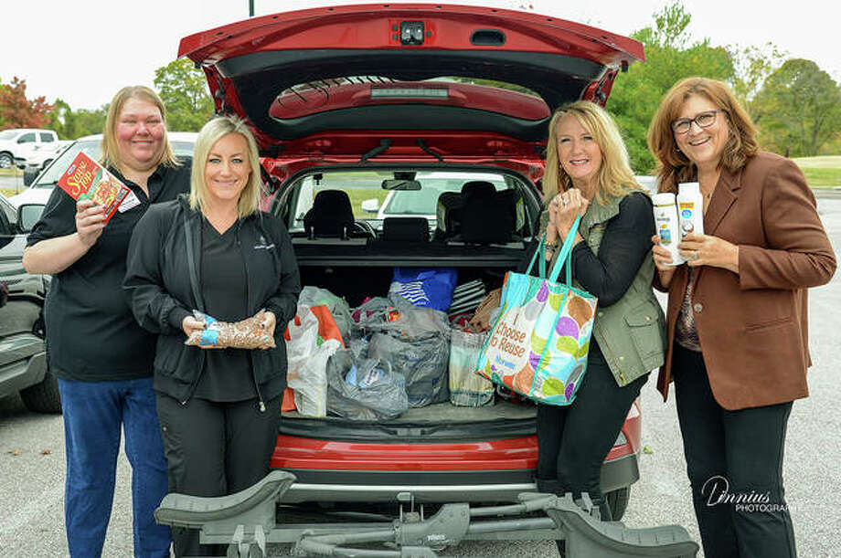 Shown with a car full of donated goods are Greta Sullivan - Olive Oils & More; Adrienne Schaefer - Soothe Massage & Bodywork; Laura Klein - Touchstone Crystal; and Teri Dinnius - Dinnius Photography. Photo: Courtesy Of Dinnius Photography