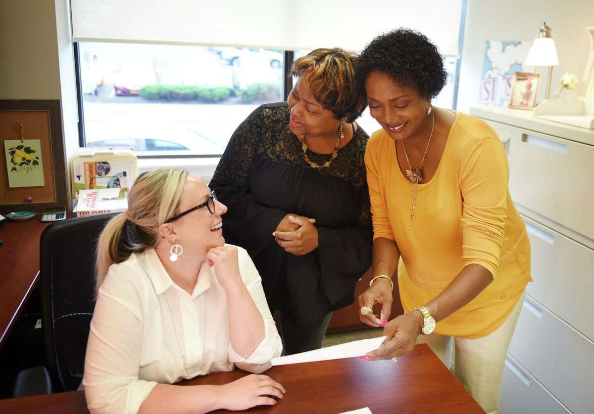 Crickett Thomas-O'Dell, regional director at Workforce Development Institute, right, works with Ana Culver, grant program manager, left, and office manager, Wanda Parsons, center, at the WDI offices on Thursday, Sept. 12, 2019, in Troy, N.Y. (Will Waldron/Times Union)