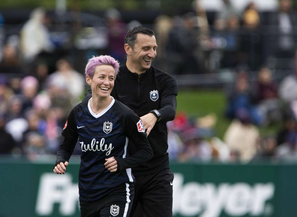 TACOMA, WA - SEPTEMBER 29: Megan Rapinoe #15 of Reign FC smiles with Reign FC coach Vlatko Andonovski after being subbed out in the second half of the game at Cheney Stadium on September 29, 2019 in Tacoma, Washington. Reign FC won 2-0. (Photo by Lindsey Wasson/Getty Images)