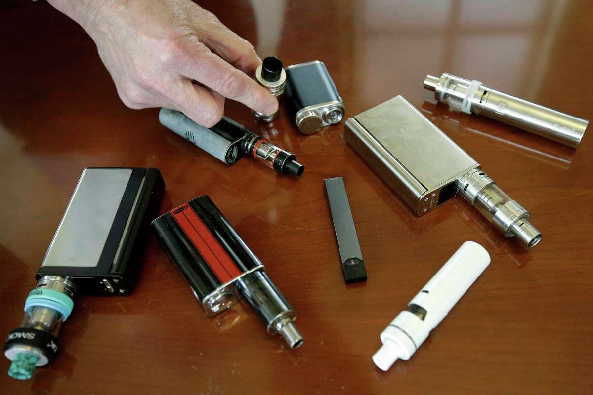 A high school principal displays vaping devices that were confiscated from students at a school in Massachusetts.