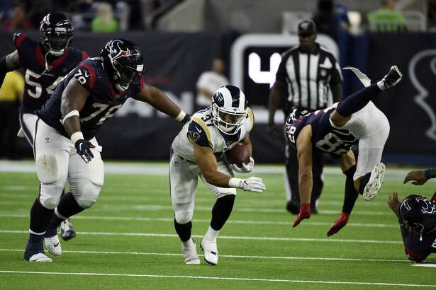 Los Angeles Rams running back Matt Colburn (37) rushes as Houston Texans' Javi Edwards (78) and Xavier Crawford (28) defend during the second half of a preseason NFL football game Thursday, Aug. 29, 2019, in Houston. (AP Photo/Eric Christian Smith)