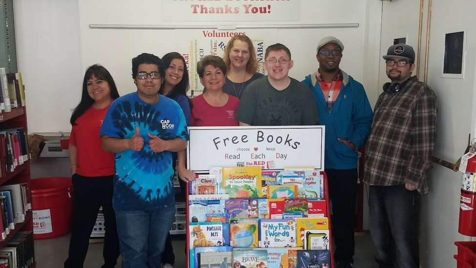 Volunteers stand in front of a RED Bookshelf, which has a variety of free children's books and can be found in waiting rooms and doctors offices.