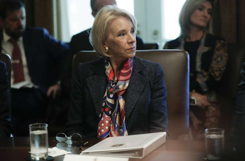 In this Oct. 21, 2019, photo, Education Secretary Betsy DeVos listens to President Donald Trump during a Cabinet meeting in the Cabinet Room of the White House in Washington. A federal judge has held DeVos in contempt of court for violating an order to stop collecting loans from thousands of former for-profit college students. (AP Photo/Pablo Martinez Monsivais)