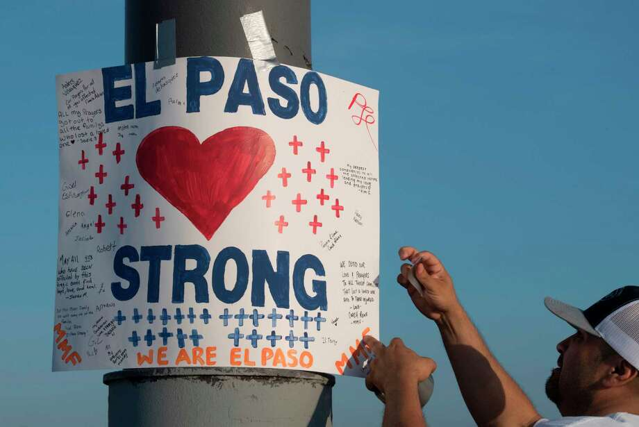"(FILES) In this file photo taken on August 06, 2019 Coach Rene installs a 'El Paso Strong' sign at the makeshift memorial for victims of the shooting that left a total of 22 people dead at the Cielo Vista Mall WalMart (background) in El Paso, Texas. - The gunman behind a shooting in Texas that killed 22 people pleaded not guilty to capital murder during his arraignment October 10, 2019, the prosecutor's office said. Patrick Crusius, 21, is accused of carrying out the August 3 mass shooting at a Walmart in the west Texas city of El Paso. He confessed to police upon his arrest and said he was targeting ""Mexicans."" (Photo by Mark RALSTON / AFP) (Photo by MARK RALSTON/AFP via Getty Images) Photo: MARK RALSTON, Contributor / AFP Via Getty Images / AFP or licensors"