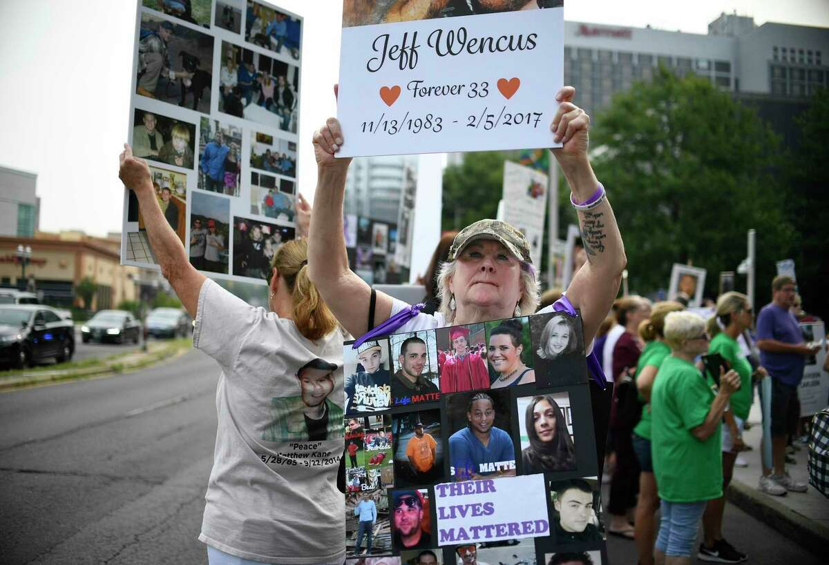 Lynn Wencus of Wrentham, Mass., holds a sign with a picture of her son Jeff and wears a sign of others' loved ones who have died from opioid overdoses, during a protest on Aug. 17, 2018, at Purdue Pharma's headquarters in downtown Stamford, Conn.